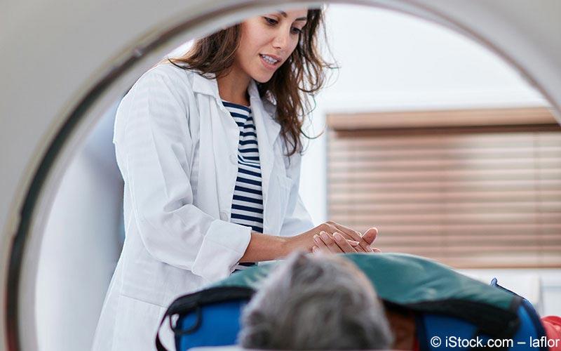 Ärztin hält Hand eines MRT-Patienten